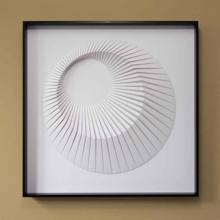 This beautiful geometric abstract wall sculpture is made out of white laser cut paper that was hand folded by Yossi Ben Abu and mound on cardboard.
