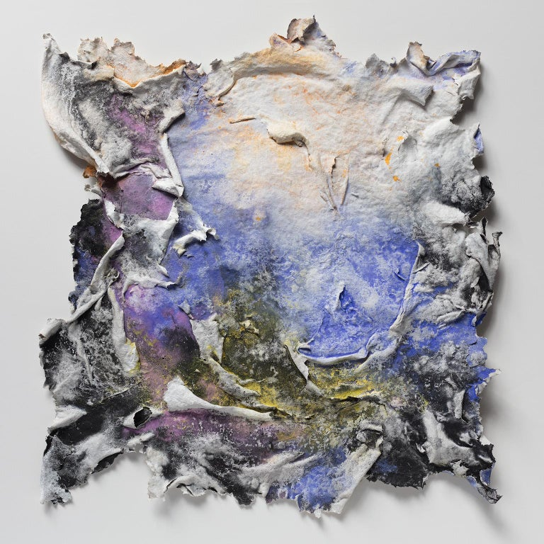 """Ruggero Vanni's """"Brumalis Dies (Winter Solstice)"""" is a 18 x 17 inch abstract work on paper mounted in a 25 x 25 inch black frame shadow box. The hand made paper is very tridimensional, with blue, yellow, and purple accents of pure pigment.  A strong"""