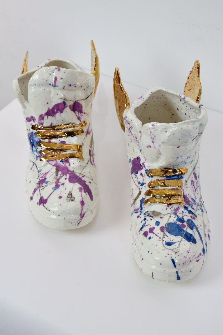 NAM TRAN (b. 1988)  Just Wing It  Porcelain with 22-carat gold lustre and paint splatter Right shoe: 14 x 10.4 x 22.8 cm (5 ¹/₂ x 4 ¹/₈ x 9 inches) Left shoe: 14.5 x 9.2 x 22.8 cm (5 ³/₄ x 3 ⁵/₈ x 9 inches) Initialled and numbered 1/1 on each