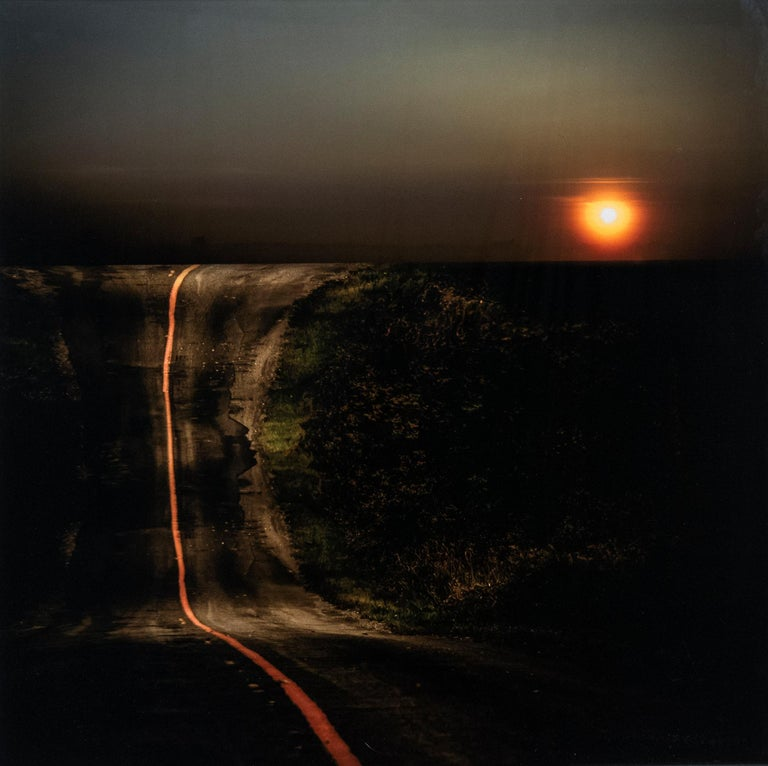 A line of fiery orange splits a dark road in two in this dramatic image by Mark Bartkiw. The sun sets on the horizon.  This C-print is sealed between dibond and plexiglass. This work is the Artist's Proof from an edition of 8.    After studies in