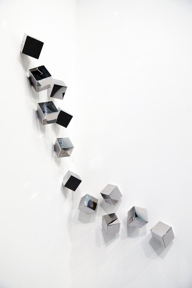 Ten cubes of polished stainless steel drift through space in this dazzling sculptural wall installation by Lori Cozen-Geller.    Cozen-Geller grew up in Los Angeles, California, and received a BA from the University of Southern California. She has