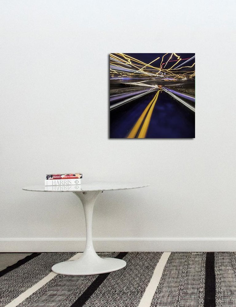 Shocks of light -- yellow , indigo, red and white -- zip through the night in this dynamic photographic print by Mark Bartkiw. This C-print is sealed between dibond and plexiglass. The work weighs 23 lbs. This work is the Artist's Proof from an