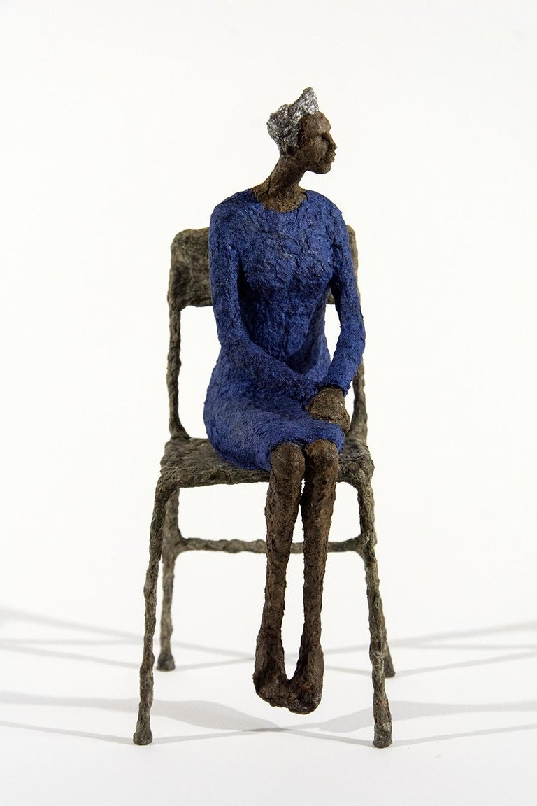 A pair of seated figures in yellow and blue wait quietly in this contemplative paper mache artwork by Paul Duval. The elongated shapes of the women and chairs are reminiscent of the expressive forms used by modernist Alberto Giacometti.  Paul Duval