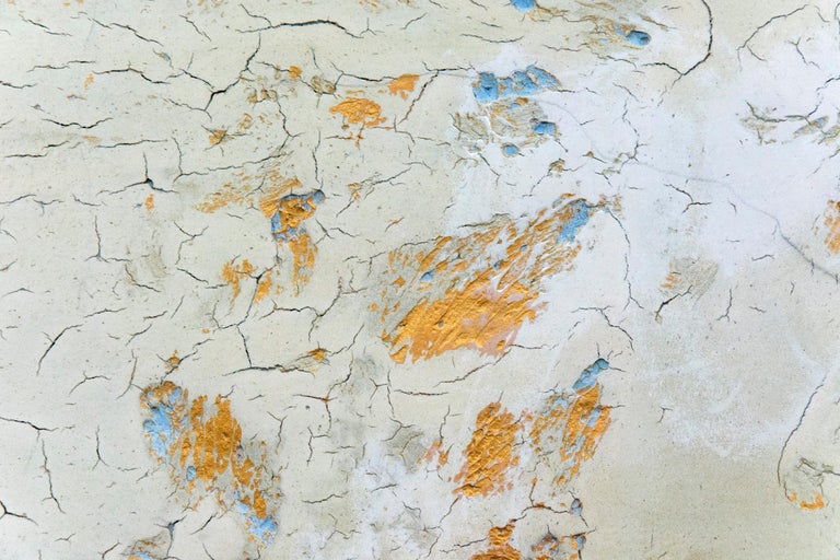 Clouds of pale blue, dove grey and and ochre merge with the tactile surface of this atmospheric plaster and pigment painting by Jutta Naim. Marks pulled by hand through the plaster, thick and cracking dynamically in areas, create a lively and