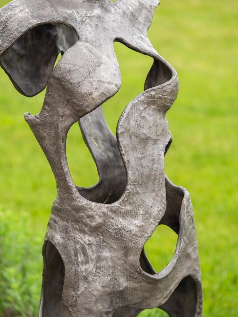 Toronto-based sculptor David Fisher explores the effects of positive and negative space in this cast bronze outdoor sculpture. With a nod to classical Greco-Roman statuary, this female figure is poised on its rectangular plinth. This work is number