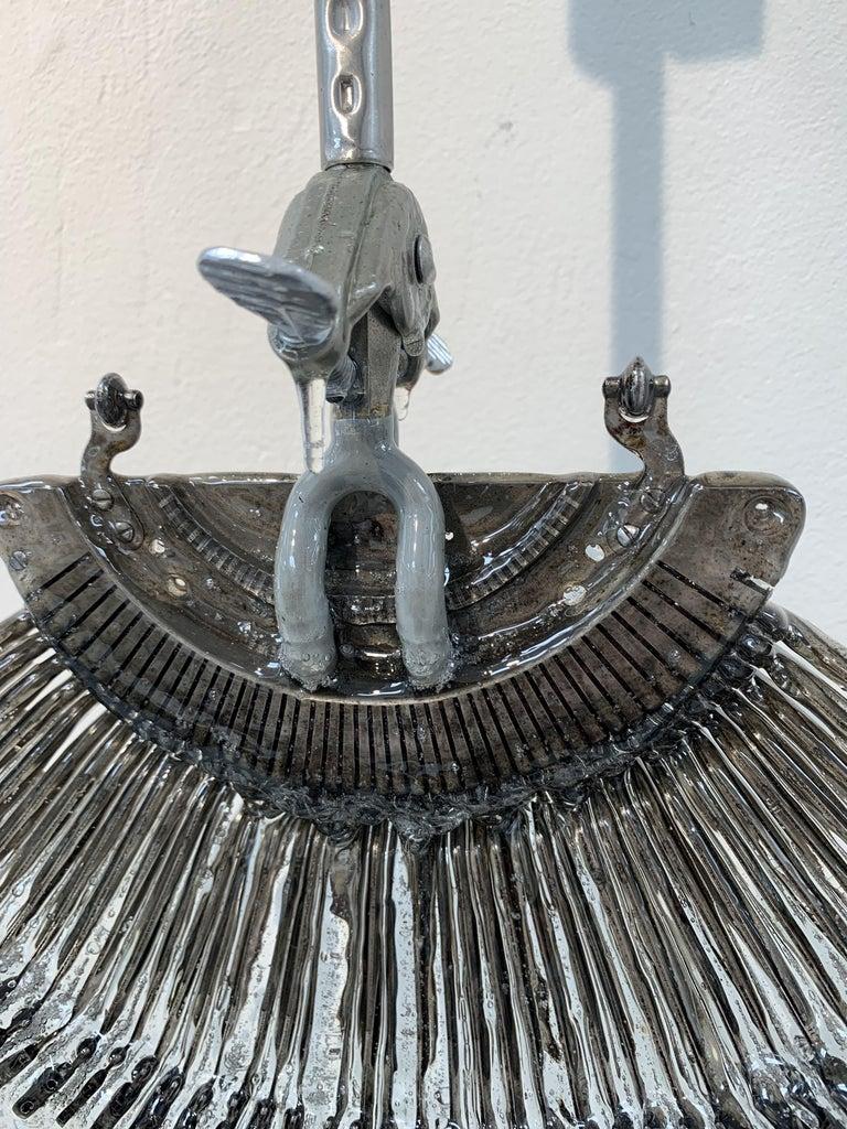 Wall sculpture made of vintage typewriter striker fan, resin, aluminum lab hardware.
