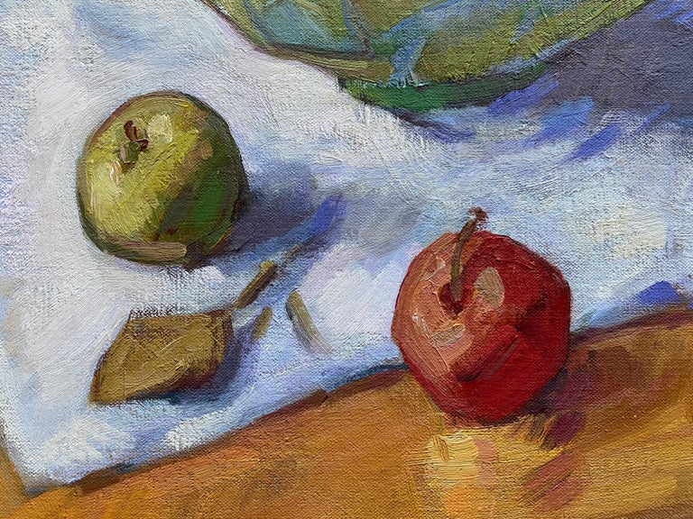An oil painting of a still life. A bowl of apples  overflows onto a wooden table, upon a simple white linen and beside a ceramic jug.  A traditional wooden chair fortifies the composition amidst a crisp blue backdrop. Painted from  life and yet
