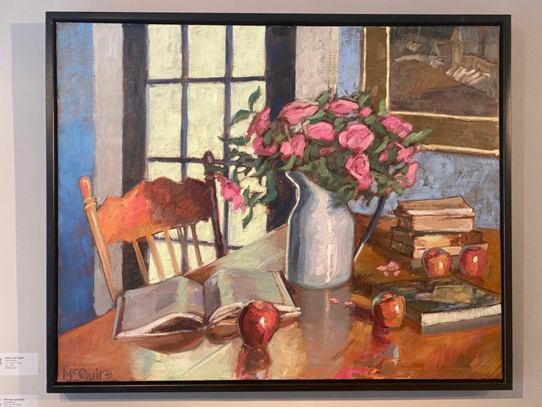 An oil painting of an interior setting featuring scattered fruit, books, an a bouquet of hot pink flowers in a white porcelain vase.  Framed in a black floating frame.  Tim McGuire Born in 1971, Tim McGuire grew up in Buffalo, NY.  After teaching