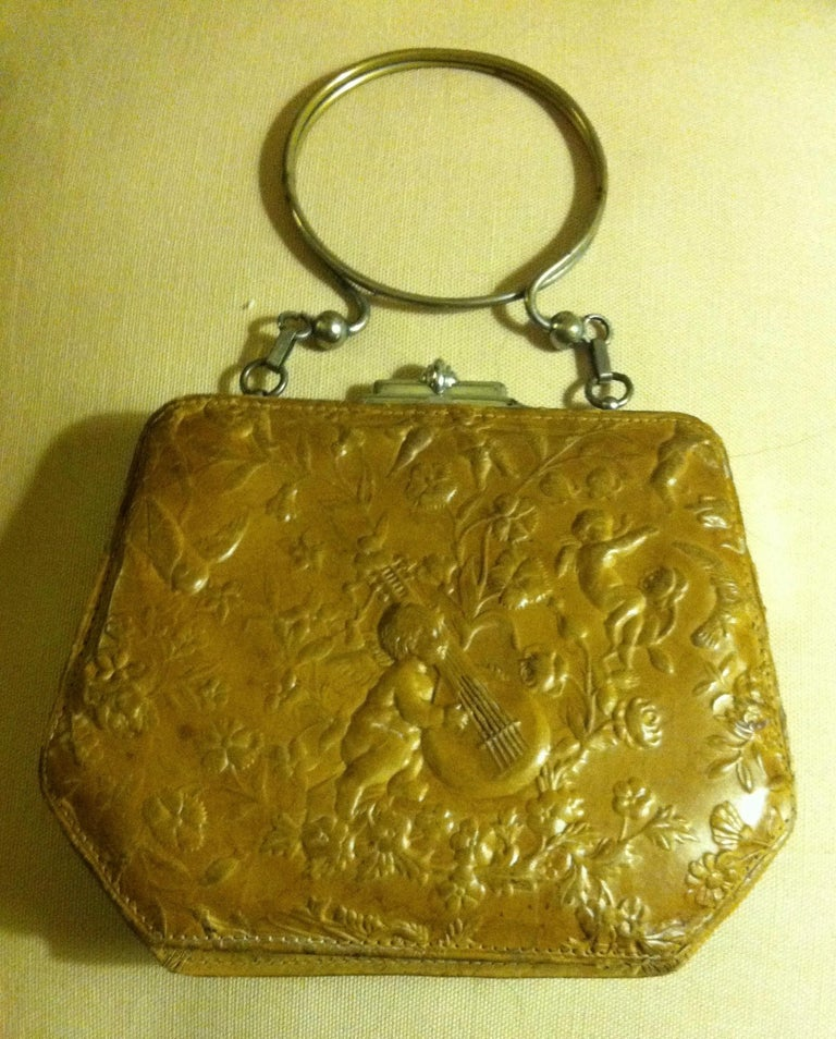 This Victorian leather embossed purse depicts a cherub playing a lute in the center, surrounded by floral elements, birds, and another cherub.  The embossed leather is caramel-colored and lined in silk of a similar shade. Both sides of the purse