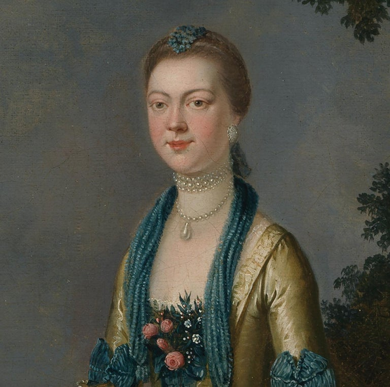 JOHN S C SCHAAK (FL 1760-1770)  PORTRAIT OF A LADY  small full length portrait in a satin gown with lace sleeves, blue bows and pearl necklace beside a fountain, a classical landscape with temple beyond Signed and dated Oil on canvas  58 x 47cm