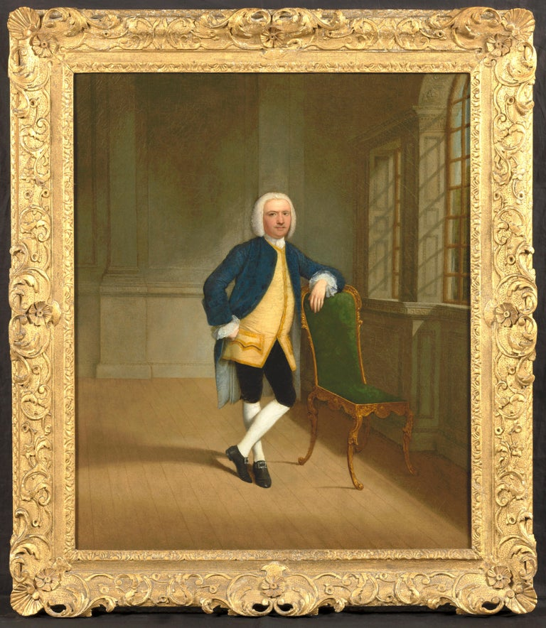 Arthur Devis 1712-1787 A gentleman in an interior leaning on a giltwood chair by a window  Oil painting on canvas 30 x 25 inches Contained in its fine carved, pierced and gilded decorated with flowers and entwined tendrils  Provenance: Sir Herbert