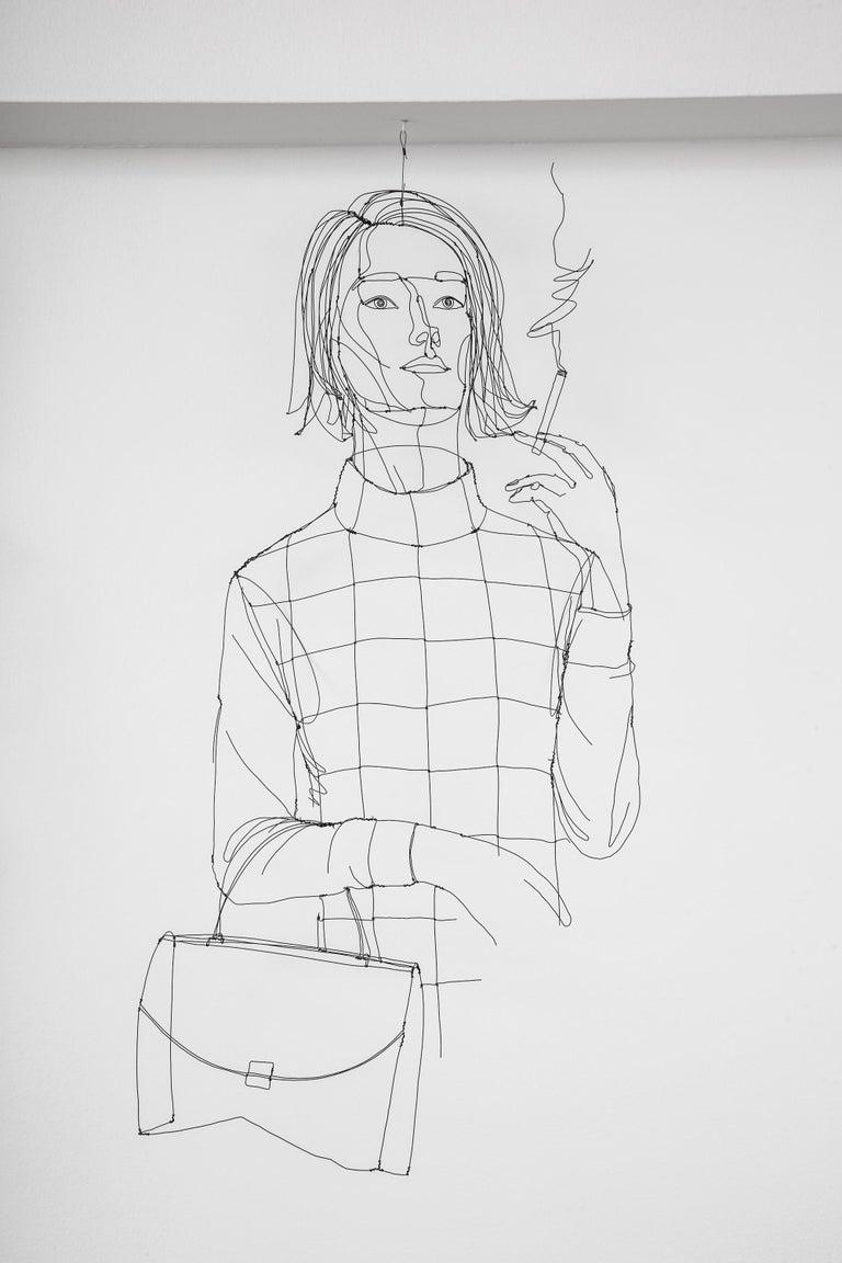 Wire sculpture of a stylish woman with handbag and cigarette created by Alexandre Bour (Nancy, France, b. 1975). The sculpture casts a drop shadow, giving a 3D effect.  Unique piece, handmade and signed in the mold by the artist.
