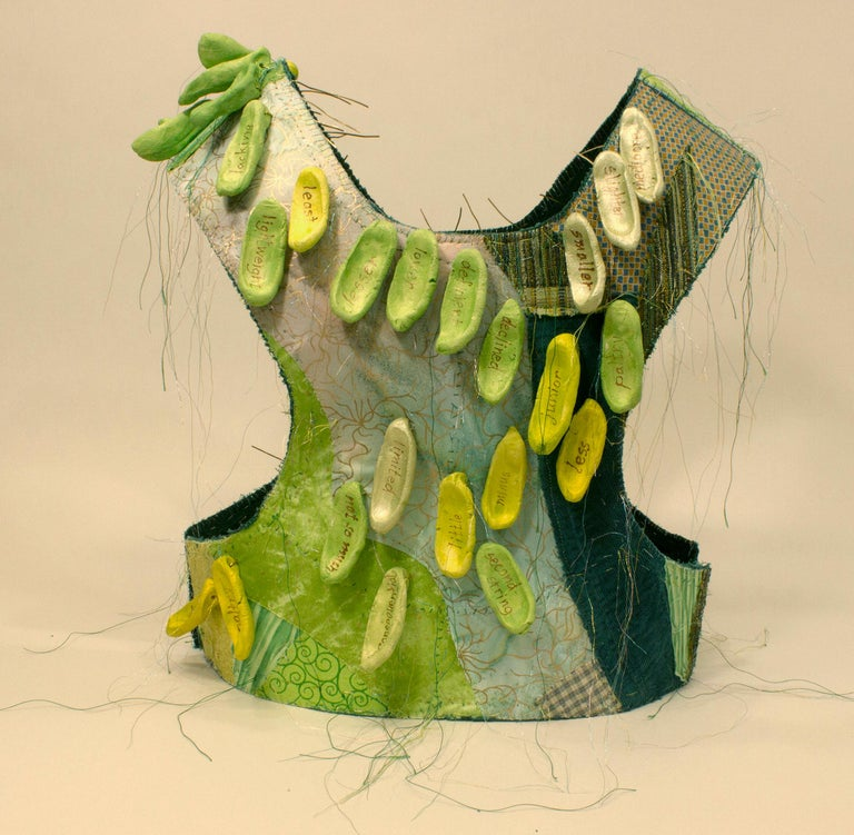 """Virginia Mahoney's """"Less"""" is a mixed-media sculpture in vest form that is primarily green with many prints and variations, and has attached ceramic tags in shades of green, on which words, referring to being less than others, are handwritten in"""