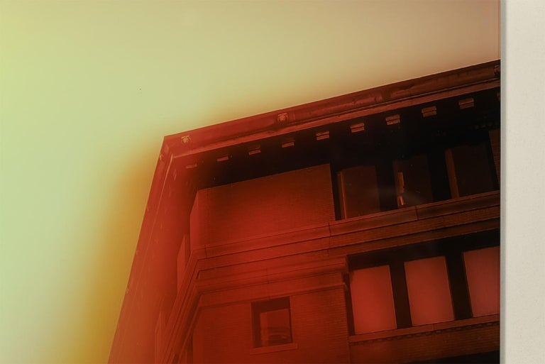 """Jeffrey Heyne's """"Melcher Street with Nickel Yellow and Rose Madder 6:07pm"""" is a toned black and white landscape photo of the architectural cornices along Boston's Melcher Street. The 16 x 24 inch photo is toned in yellow and orange/red, and blurred"""