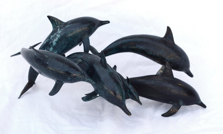 "Bronze sculpture of a pod of Dolphins by Winston Walter Carmean (American, 1925-2010). Signed, numbered, and dated ""W. W. Carmean  11/50  1982"" on the underside of one of the dolphins. The small edition of dolphins was a special commission for the"