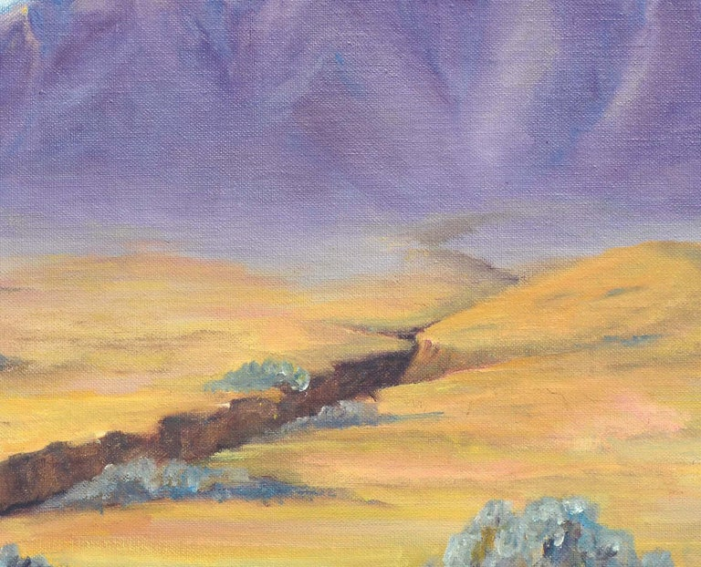 Sweeping desert landscape with a colossal purple mountain range in the distance by Alice M. Fink (American, b1880s-1968). Signed