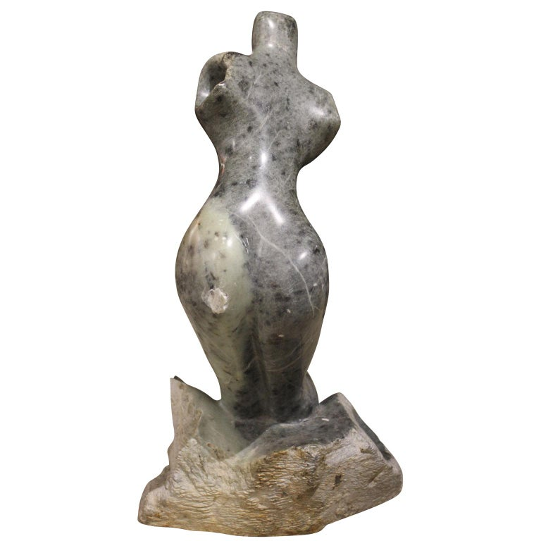 Figurative sculpture of a nude female figure. The stone is a grey tone with speckling. The artist signed and dated the piece in the crevice on the bottom. Jose Zacarias is known for producing abstract figurative sculptures.