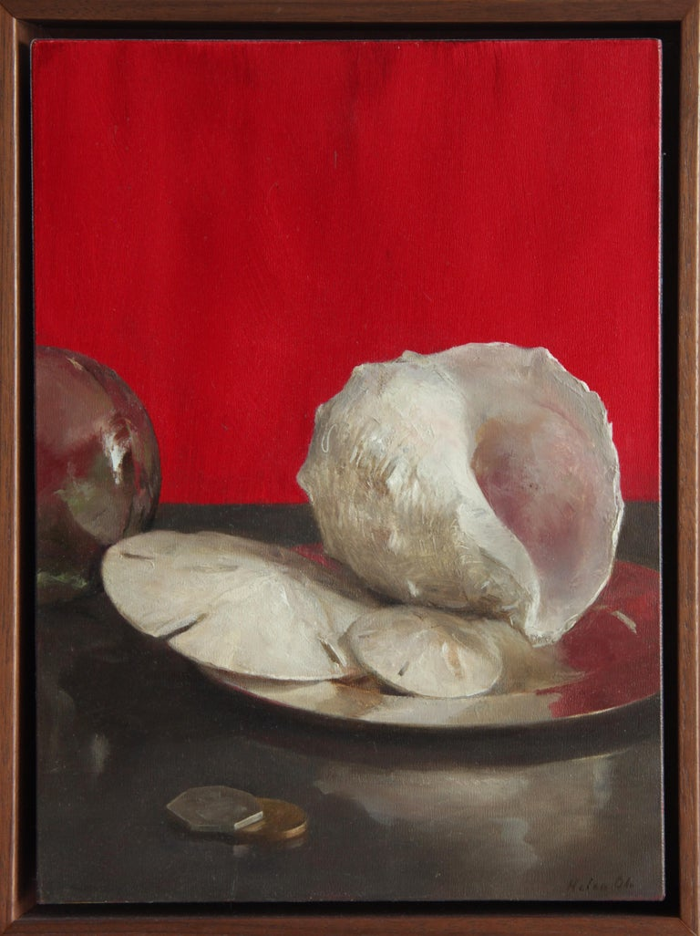 The inherently beautiful sand dollars and sea shells are arranged on a silver tray and flanked by coins and a reflective orb. The background is a vibrant red reflecting itself on the edge of the silver tray.  This artwork is framed in a simple