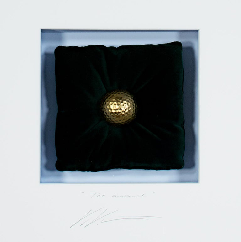 """The Award"" is an original mixed media artwork by Volker Kuhn. The artist signed and titled the piece below the artwork on the mat. It features a golden golf ball on a black velvet pillow.   6 3/4"" x 6 3/4"" art 20"" x 19"" frame  Volker Kuhn spent his"