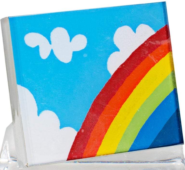 """Rainbow Pin"" is an original limited edition serigraph on plexiglass with a metal backing and a locking bar pin closure. The edition, signature, and date are engraved on the verso.  The pin features a cheerful rainbow in the lower right corner"