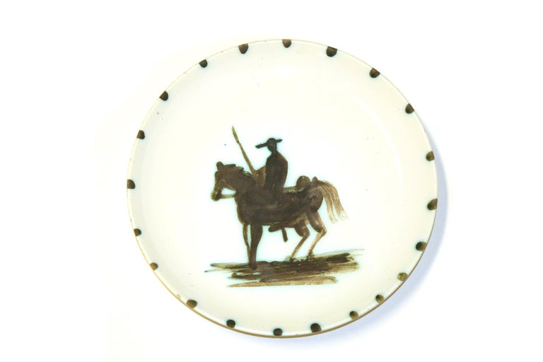 Picador is a wonderful hand-painted ceramic realized in 1952 by Pablo Picasso. From a limited edition of 500 pieces. With a diameter of 20.5 cm, this beautiful ceramic dish has at the center a black silhouette of a picador, i.e. the first knight of