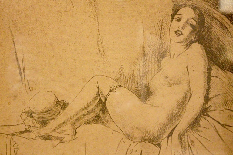 A nicely executed 1920's nude study in pencil and charcoal. The female nude wearing stockings and shoes reclining on a bed with clothes and hat at her feet. Framed and glazed.