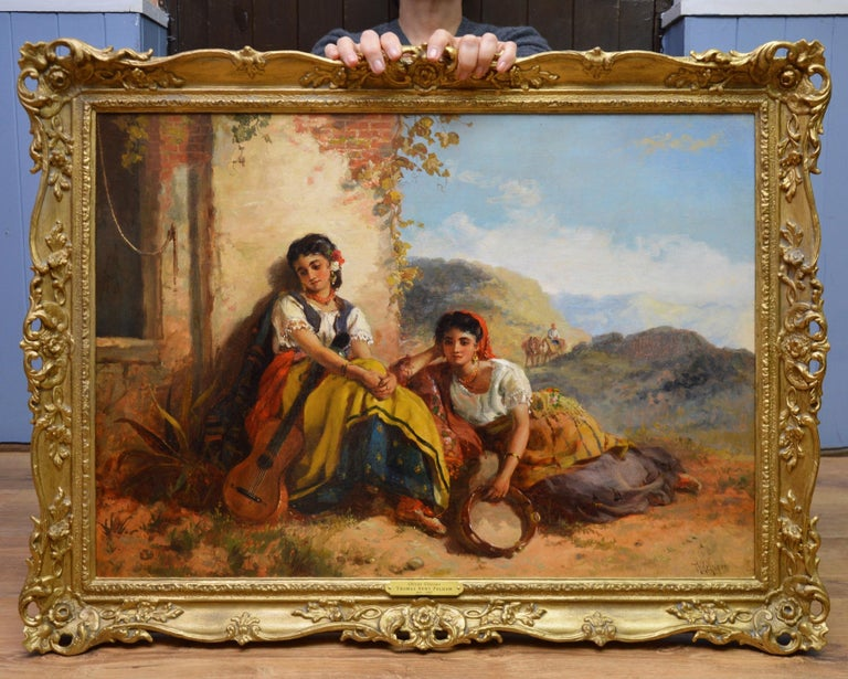 This is a large fine 19th century oil on canvas depicting a pair of young Spanish girls with a guitar and tambourine resting in the shade by the eminent Royal Academy painter Thomas Kent Pelham (1831-1907). 'Chicas Gitanas' is signed by the artist