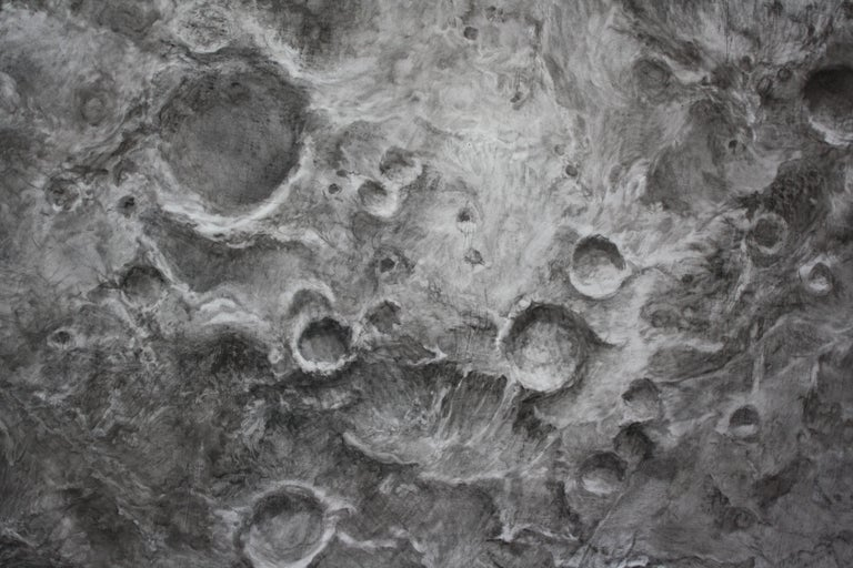 Bethany Carlson's photo-realistic charcoal drawing on a round panel. The image is of a moon or a planet in space.  More information below:  While thinking about the nature of a moon, I created works that reflect the gentle tug our moon has on our