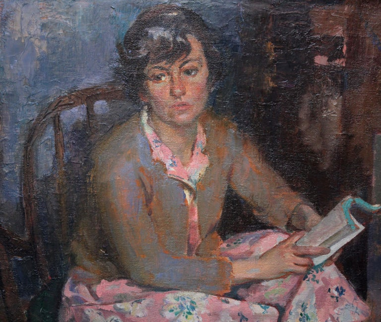 This lovely female portrait oil painting is by Scottish artist Gordon Stewart Cameron and was painted circa 1950. The portrait is of a woman in a pink floral dress sat reading by a fire, slippers warming. She is glancing away from her book as if in