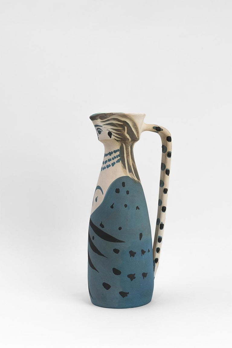 Turned pitcher (A.R. 301) Inscribed 'Edition Picasso', numbered '122/200' and stamped 'Madoura Plein Feu / Edition Picasso' on base White earthenware clay, decoration in engobes and engraved Blue, grey, black Height: 11 1/2 inches Executed in an