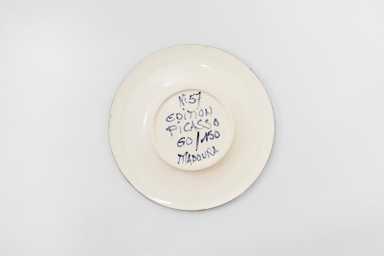 Round plate (A.R. 468) Inscribed 'Edition Picasso', 'Madoura', titled and numbered '60/150' on reverse White earthenware clay, decoration in engobes and enamel under partial brushed glaze Blue, pink, red, white, black Diameter: 10 inches Executed in