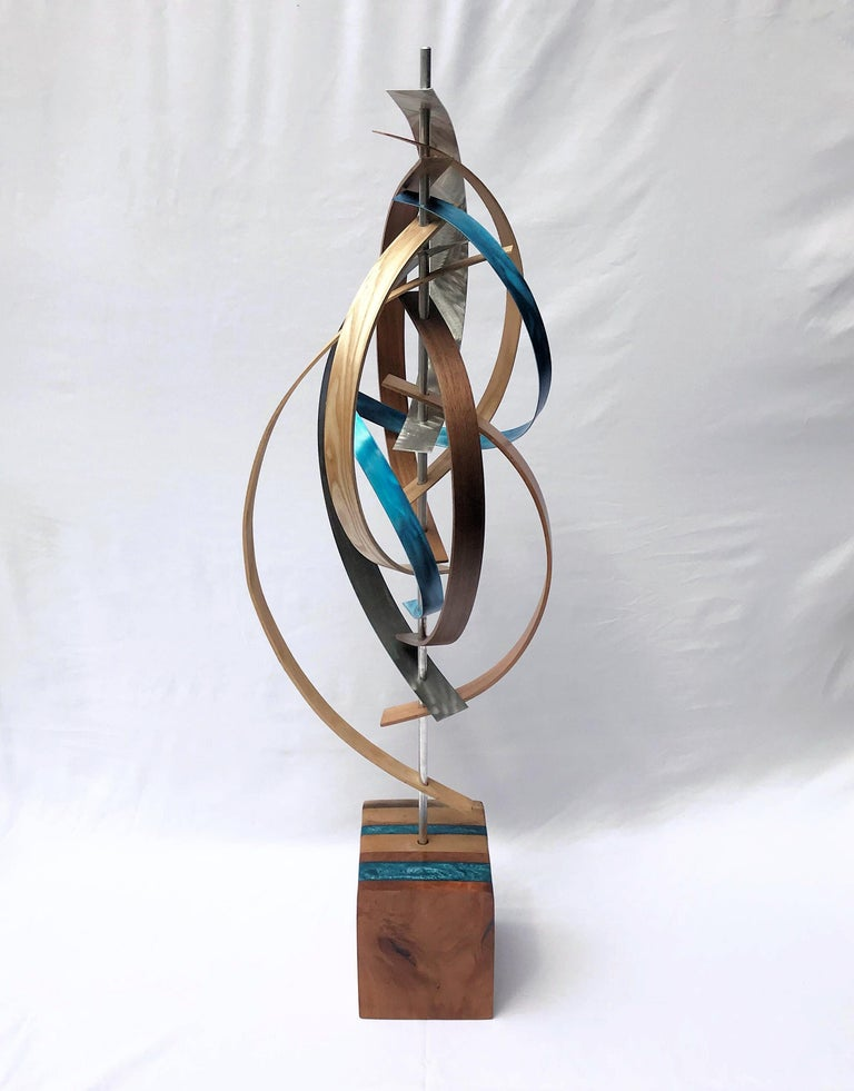 Title: Confetti Description: Black walnut, cherry, and ash slats pairs nicely with ground aluminum of complementary hues and braided about an aluminum rod. The base is an extension of the bent wood top with accents of blue epoxy inlay.  About the