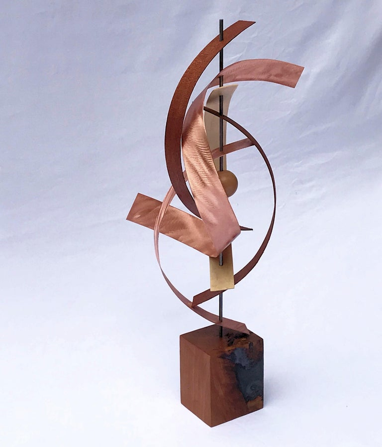 Title: Woven Description: Black walnut, hickory and mahogany bent into place with bent copper whirling throughout, holding in place a wooden sphere.    About the Artist: Jeff Linenkugel was born and raised in Toledo Ohio and is a graduate of Ohio