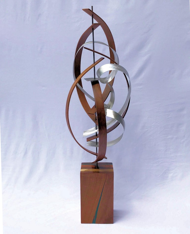Title: Bubbly Description: Black walnut slats bent about a steel rod with bubbling ground aluminum accent strips. Sculpture base features laminated walnut, cherry, poplar with a turquoise epoxy inlay and a satin finish.  Jeff Linenkugel was born and