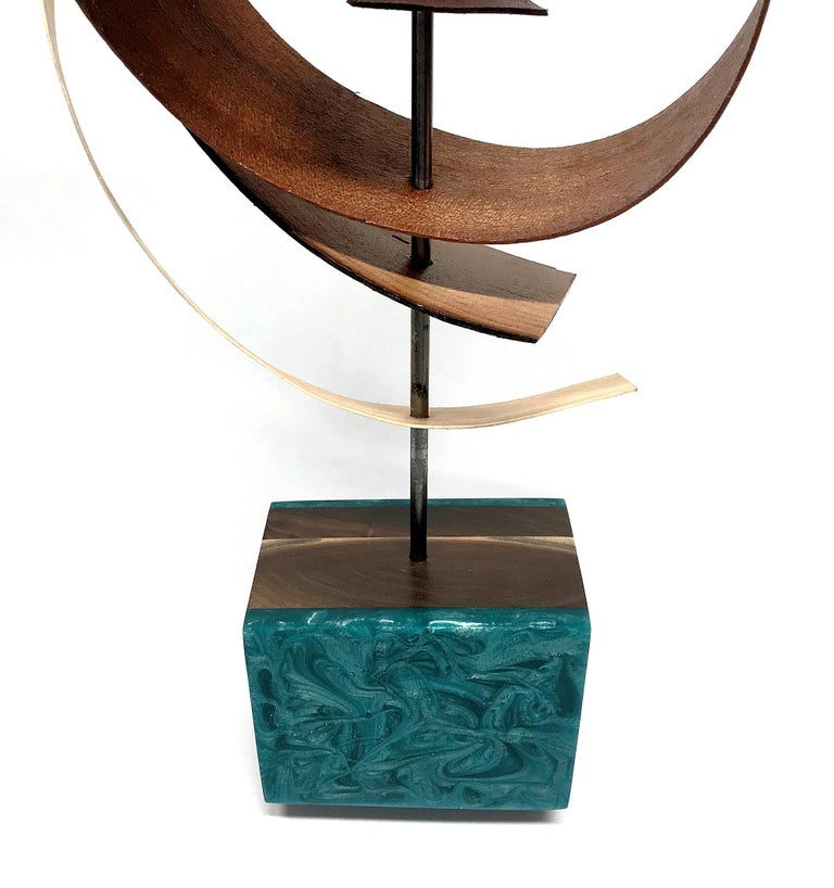 This Mid-Century Modern Inspired Wood Sculpture is comprised of pine and mahogany slats woven about a steel rod and sits atop a black walnut base which features green/blue epoxy accents.  Title: Ribbon Artist: Jeff Linenkugel  About the Artist: Jeff