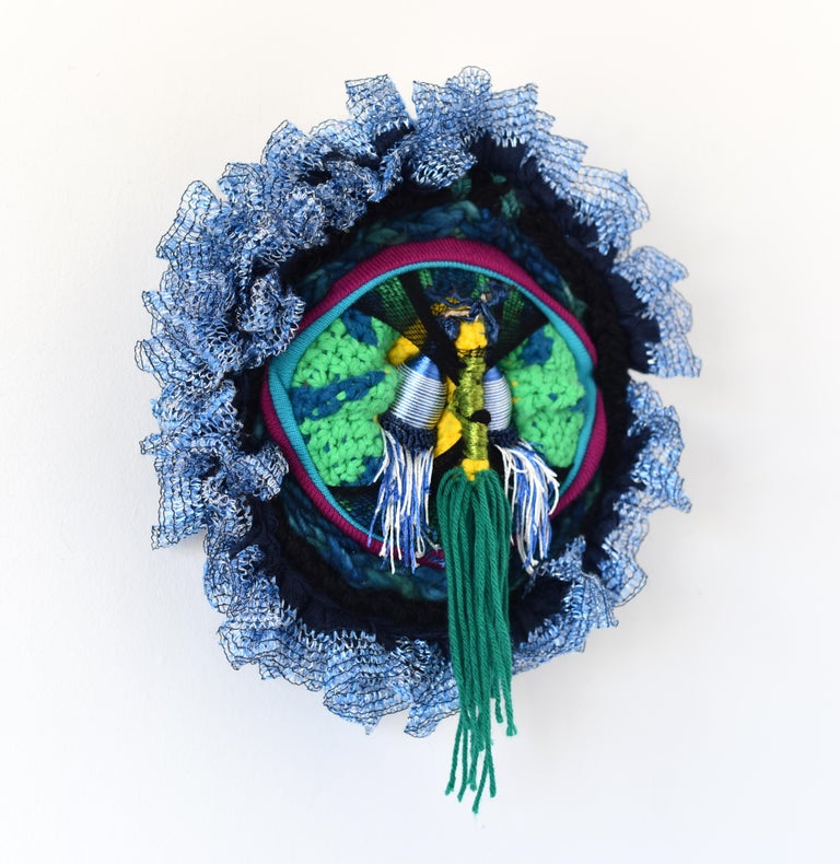 Der Nachtwächter is an abstract circular wall sculpture made with is made up of garments, nylon, yarn, tie-back holders and thread. Layers of fabric serves as a substitute for paint, creating an intense illusion of space with an ambiguous foreground