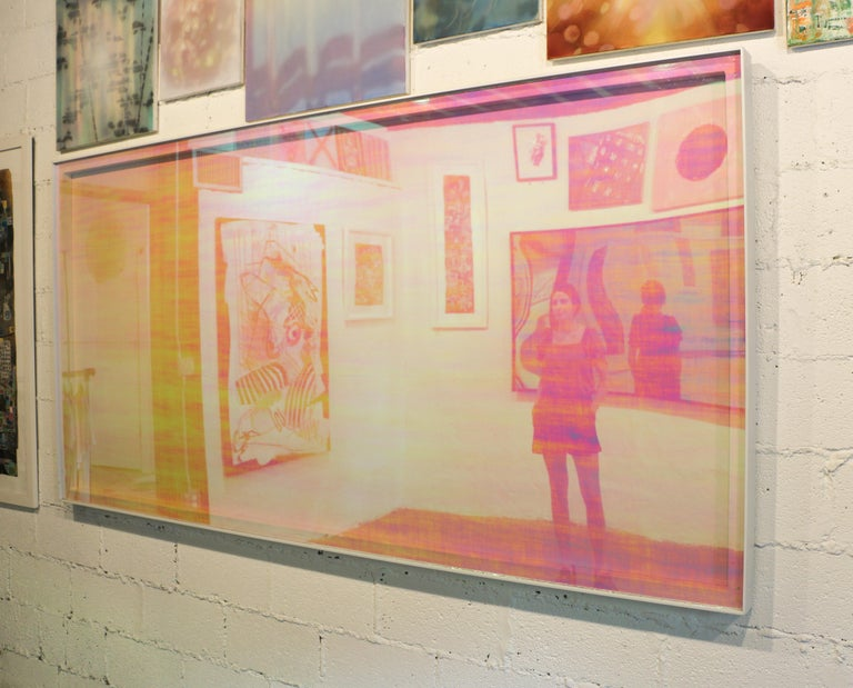 In this piece, Marcus Manganni has mounted a large sheet of cast acrylic covered with a light pink polychromic vinyl in a white aluminum frame,  which stares back at viewers as they see themselves in the reflection.