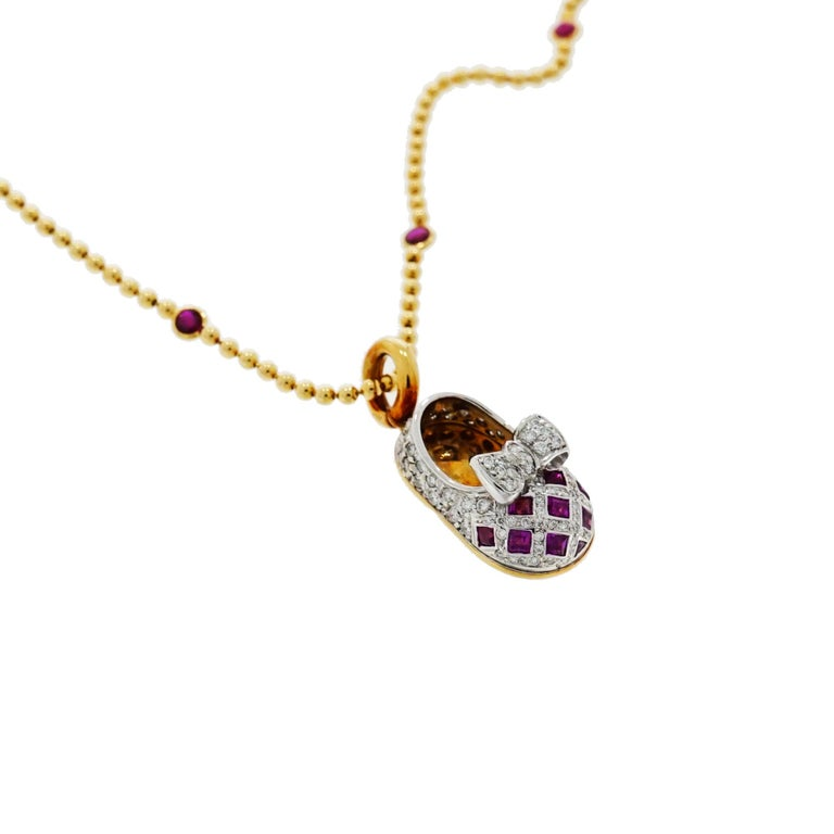 The Aaron Basha baby shoe charms are synonymous with quality, fashion and playful.  This Baby Shoe is bejeweled with Rubies and Diamonds, crafted in 18k Yellow Gold. Complemented by an 18k Yellow Gold Beaded chain with 7 bezel set round Rubies. The