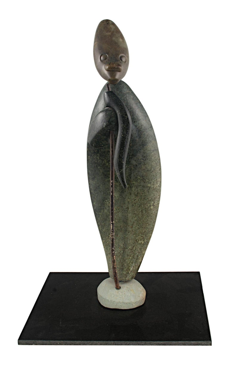 """""""Drover"""" is an original yellow & green opal serpentine stone sculpture by Aaron Perkins Chikumbirike, a contemporary Shona stone sculptor. The artist signed the piece. It depicts an abstracted herder.   20"""" x 5"""" x 4 1/4""""   Born in Wedza District,"""