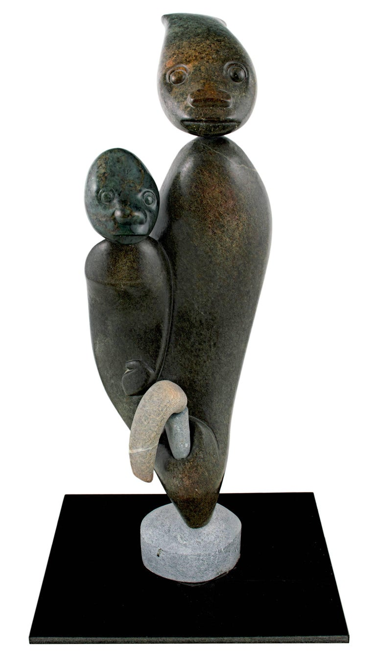 """Healing and Diagnosing"" is an original springstone and fruit serpentine stone sculpture by Aaron Perkins Chikumbirike, a contemporary Shona stone sculptor. This sculpture depicts a healer helping a young person.   22"" x 7 1/4"" x 4"" art  Born in"