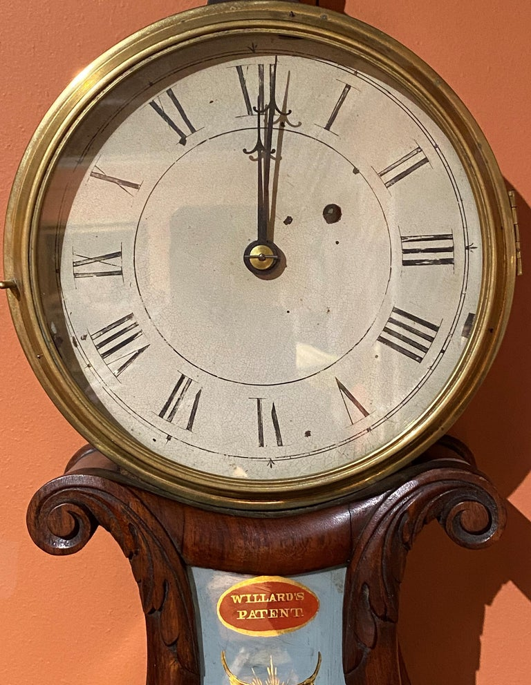 A fine Willard's Patent lyre form wall clock in carved mahogany case by Aaron Willard (1757-1844) with carved foliate finial, 7 inch Roman numeral hand painted dial, original reverse painted glass throat panel featuring two battling tall ships,