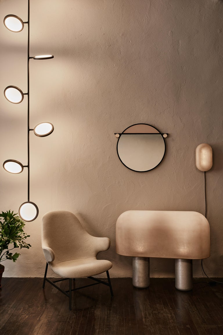 The Abal mirror collection consists of three simple geometries- round, capsule and rectangle. Made in a range of sizes, each mirror is visually segmented by a metal frame dividing the mirror from a panel of painted glass.