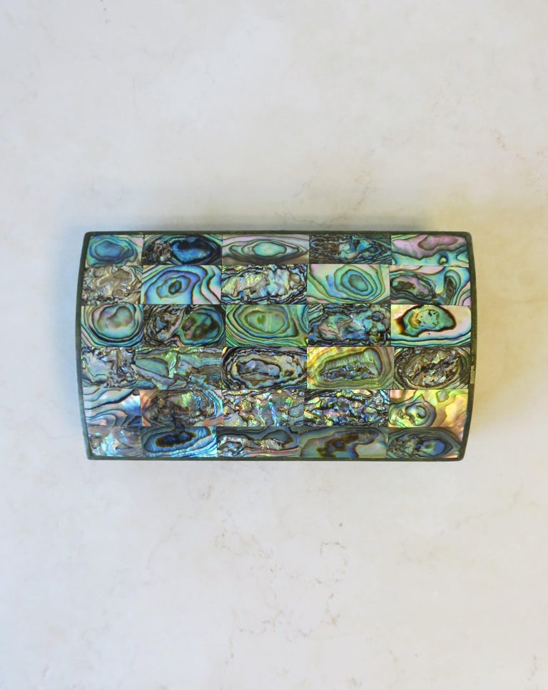A beautiful abalone seashell/sea shell box. Beautiful iridescent blues, greens, and pinks. Great as a standalone piece or for small jewelry/other small items on a desk, vanity, nightstand table, etc. Box measures: 2.75