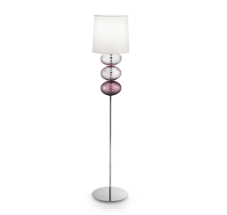 Abat Jour floor lamp with white fabric shade, chromium-plated stand and handmade blown glass elliptical elements. Its combination of white and color make it a subtle yet playful addition to any room. Also available in other colors and as a table