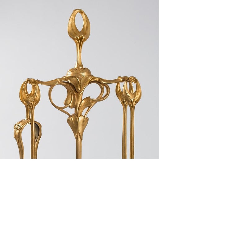 A French Art Nouveau gilt bronze fireplace set by Abel Landry. The five-piece set comprises a stand, brush, tongs, poker and shovel. All pieces decorated in repoussé vegetal and floral motif with stylized calla lily finial and accessory handles,
