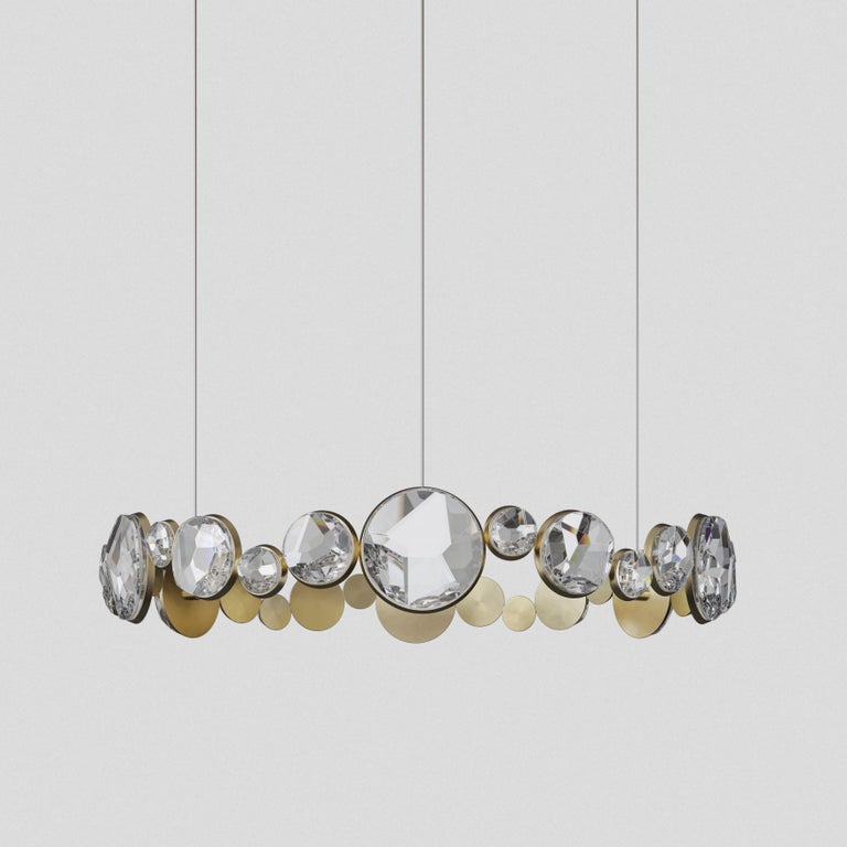 Equalling magic and mystery, Abracadabra ceiling light delivers enchanting properties. Round cut diamonds hypnotically aligned forming a ring and magically suspended by gold brass chains. Sourced in Germany, this crystal glass is handcut to
