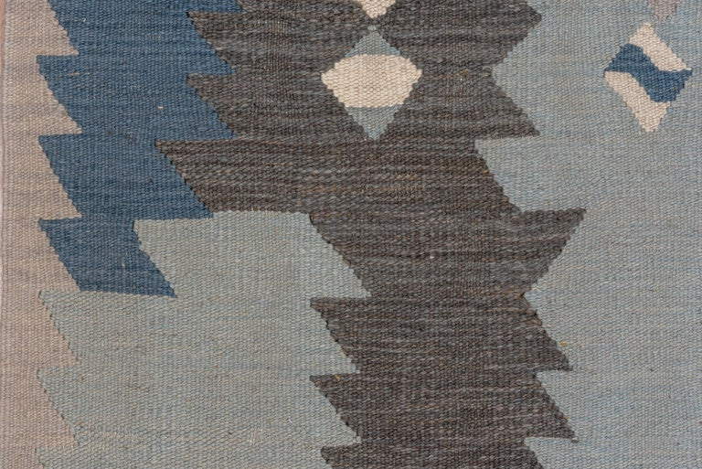 A palette featuring a range of mellow blues and touches of gray Slit tapestry weave, wool pattern wefts. More tonally bold, but with a pattern of diminutive lozenges and dominating sawtooth motives. Narrow triangle zig-zag border. As new condition.