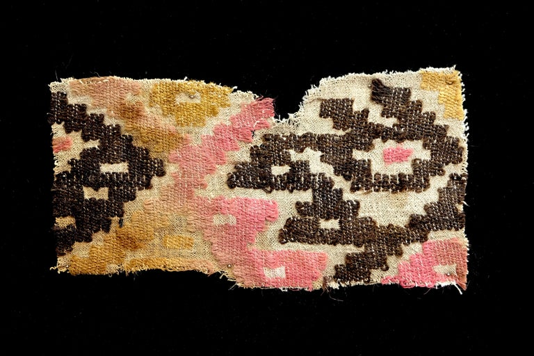 Beautiful brown, pink and crème pre-Columbian textile fragment with geometric avian figure. This piece is mounted on a black shadow box.