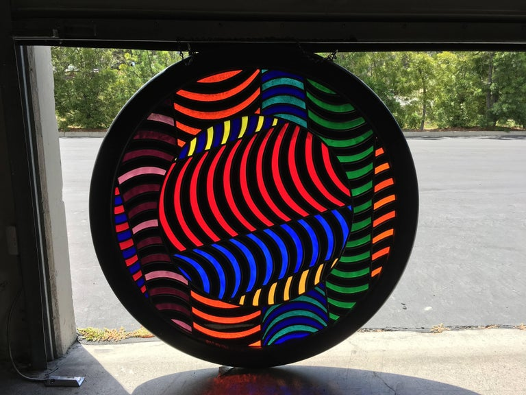 Round abstract design stained glass window in a ebonized oak frame.