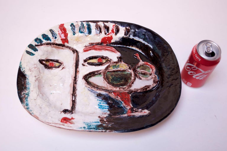 Masterful, large Italian ceramic charger depicting an abstract face with martini. Bold colors and a combination of both flat hand painted and raised decoration give the piece added depth / dimension. There appears to be minor loss to the bridge of